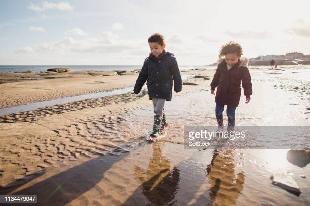 exploring the beach with her brother - whitley bay stock pictures, royalty-free photos & images