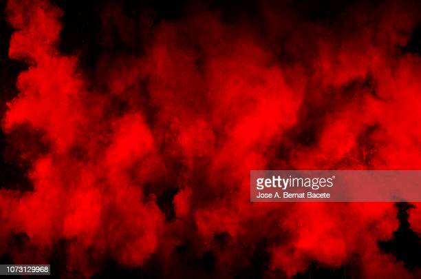 explosion by an impact of a cloud of particles of powder and smoke of color red and black  background. - rosso foto e immagini stock