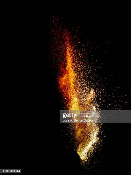 explosion by an impact of a cloud of particles of powder and smoke of color orange on a black background. - meteor crater stock pictures, royalty-free photos & images