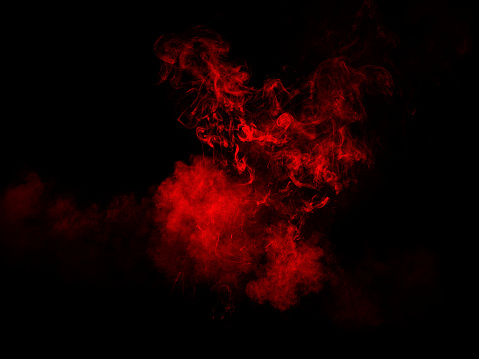 Explosion by an impact of a cloud of particles of powder and smoke of color red on a black background. - gettyimageskorea