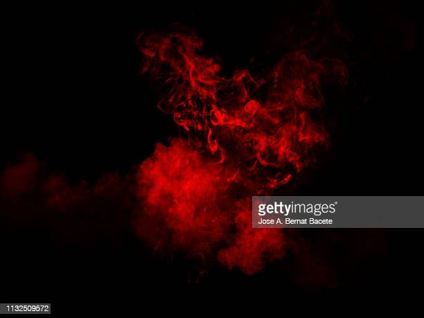 explosion by an impact of a cloud of particles of powder and smoke of color red on a black background. - bildeffekt stock-fotos und bilder