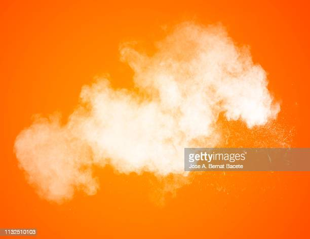 explosion by an impact of a cloud of particles of powder and smoke of color white on a orange background. - orange background stock pictures, royalty-free photos & images