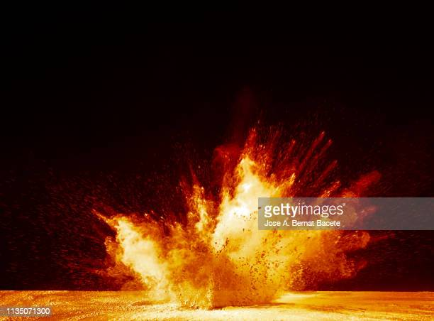 Explosion by an impact of a cloud of particles of powder and smoke of color yellow and orange on a black background.