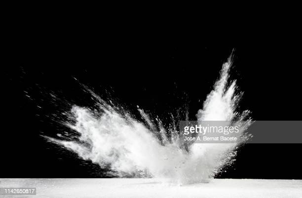 explosion by an impact of a cloud of particles of powder and smoke of color white on a black background. - impact stock pictures, royalty-free photos & images