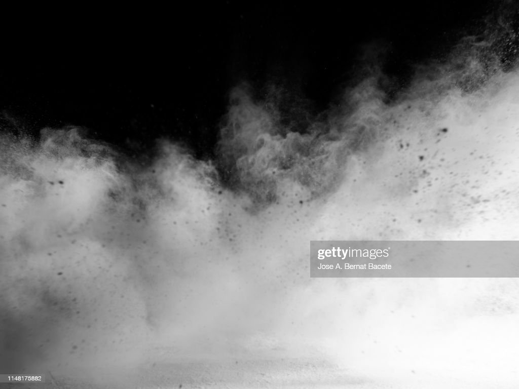 Explosion by an impact of a cloud of particles of powder and smoke of color white on a black background. : Stock Photo