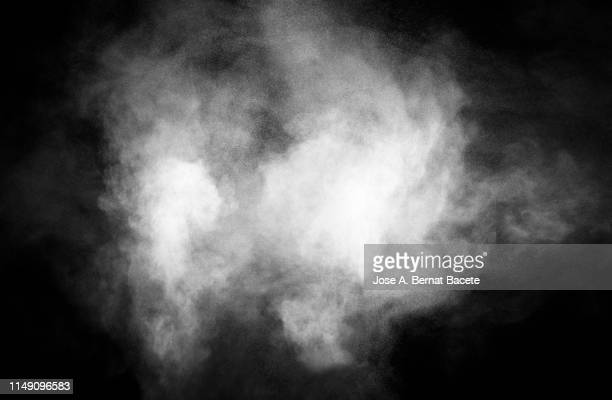 explosion by an impact of a cloud of particles of powder and smoke of color white on a black background. - {{relatedsearchurl(carousel.phrase)}} stock-fotos und bilder