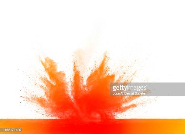 explosion by an impact of a cloud of particles of powder and smoke of color orange on a white background. - mushroom cloud stock pictures, royalty-free photos & images