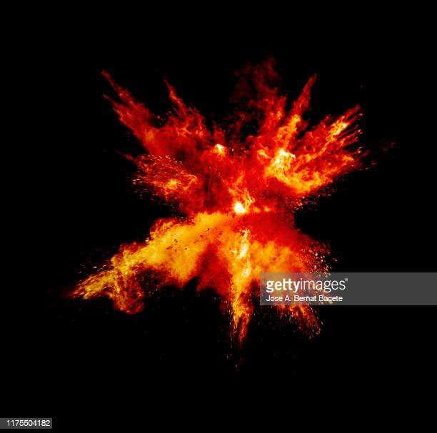 explosion by an impact of a cloud of particles of powder and smoke of color orange and yellow on a black background. - brennen stock-fotos und bilder