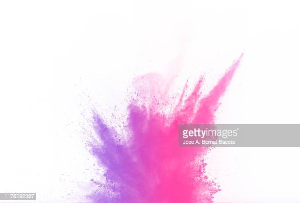 explosion by an impact of a cloud of particles of powder and smoke of pink color on a white background. - explosive material ストックフォトと画像