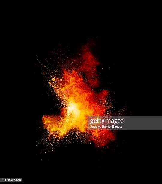 explosion by an impact of a cloud of particles of powder and smoke of color orange and yellow on a black background. - 爆破 ストックフォトと画像