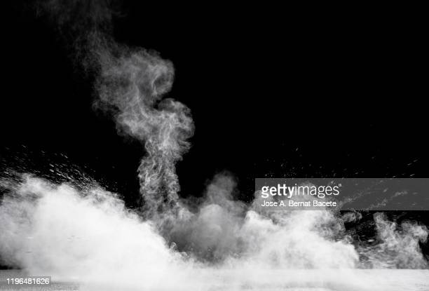 explosion by an impact of a cloud of particles of powder and smoke of white color on a black background. - 煙 ストックフォトと画像