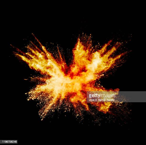 explosion by an impact of a cloud of particles of powder and smoke of color orange and yellow on a black background. - explosive stock pictures, royalty-free photos & images