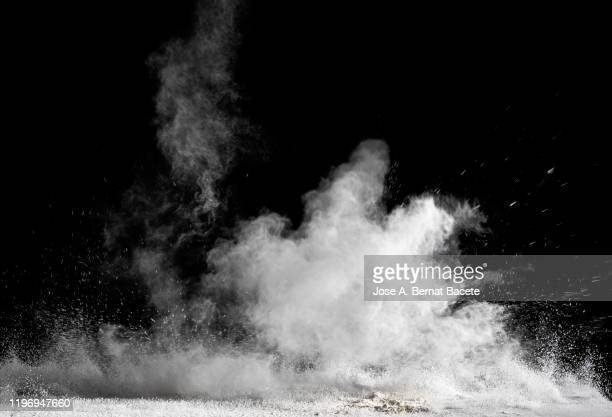 explosion by an impact of a cloud of particles of powder and smoke of white color on a black background. - fumo materia foto e immagini stock