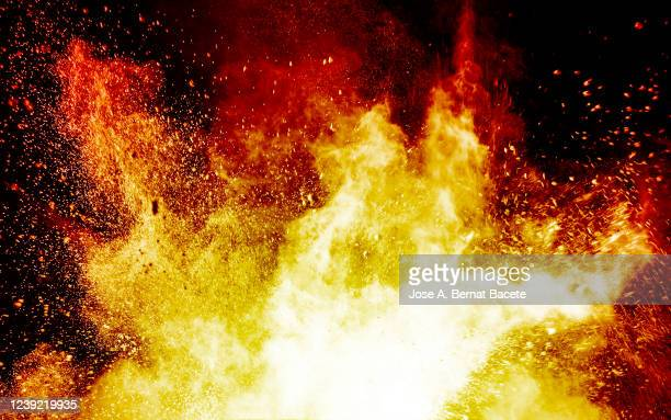 explosion by an impact of a cloud of particles of powder and smoke of color orange and yellow on a black background. - shooting a weapon stock pictures, royalty-free photos & images