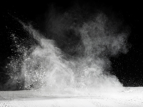 Explosion by an impact of a cloud of particles of powder  of color white and a black background - gettyimageskorea