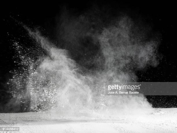 explosion by an impact of a cloud of particles of powder  of color white and a black background - blanco color fotografías e imágenes de stock