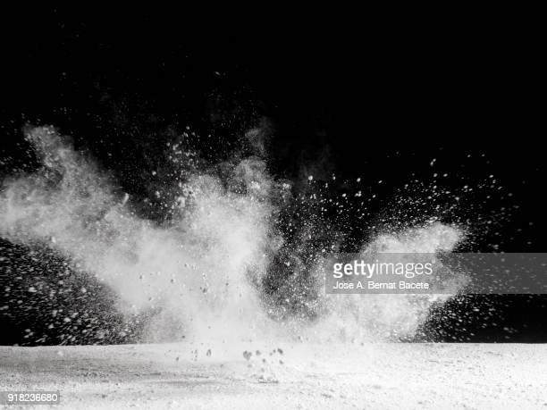 Explosion by an impact of a cloud of particles of powder  of color white and a black background