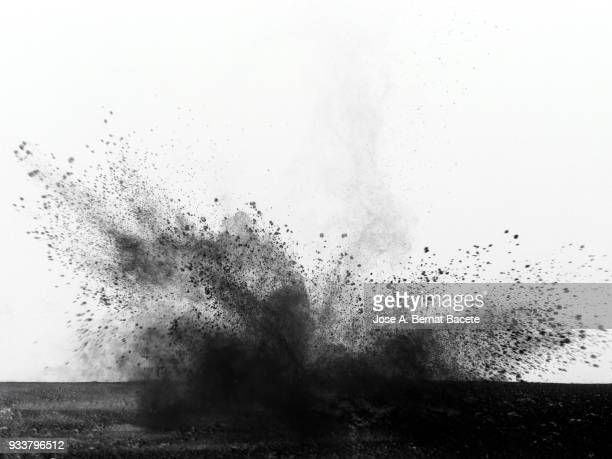 Explosion by an impact of a cloud of particles of powder of color black and a white background.