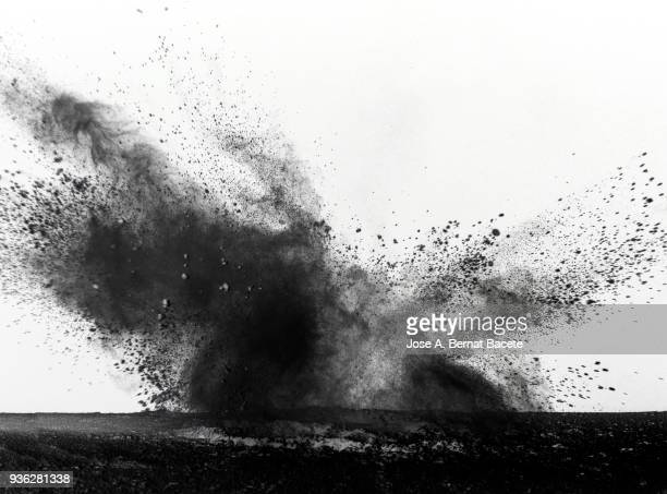 Explosion by an impact of a cloud of particles of powder  of color black and a white background