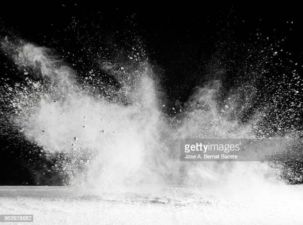 explosion by an impact of a cloud of particles of powder of color white and a black background - colour and abstract and impact not people stock photos and pictures