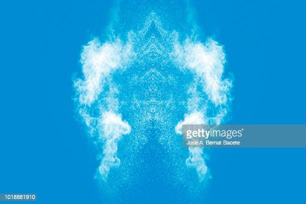 Explosion by an impact of a cloud of particles of powder of color white on a soft blue background.
