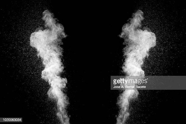 Explosion by an impact of a cloud of particles of powder of color white on a black background.
