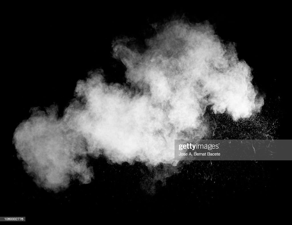 Explosion by an impact of a cloud of particles of powder of color white on a black background. : Stock Photo