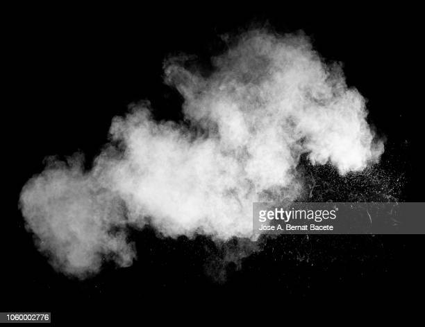 explosion by an impact of a cloud of particles of powder of color white on a black background. - fumo materia foto e immagini stock