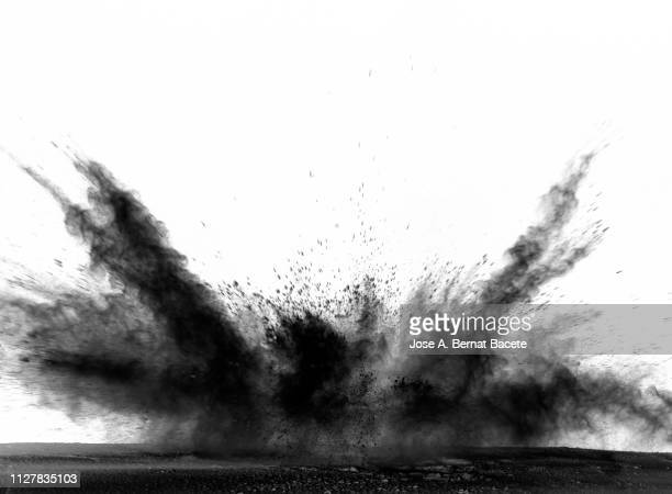 explosion by an impact of a cloud of particles of powder of color black on a white background. - schwarz farbe stock-fotos und bilder