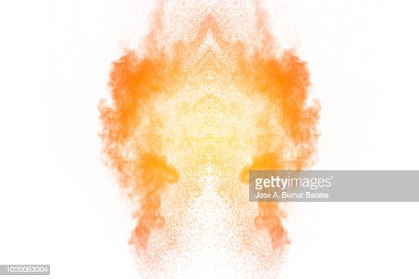 Explosion by an impact of a cloud of particles of powder of color orange and pastel colored on a white background.