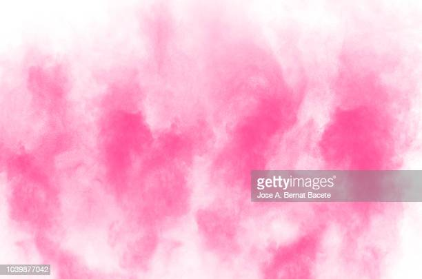 Explosion by an impact of a cloud of particles of powder of color pale pink on a white background.
