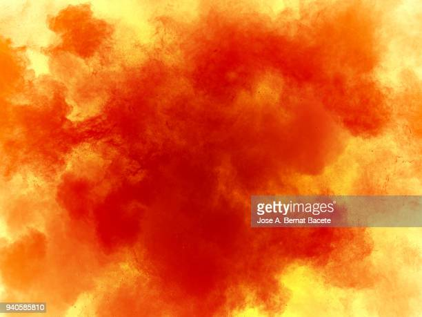 Explosion by an impact of a cloud of particles of powder of color orange and yellow background.