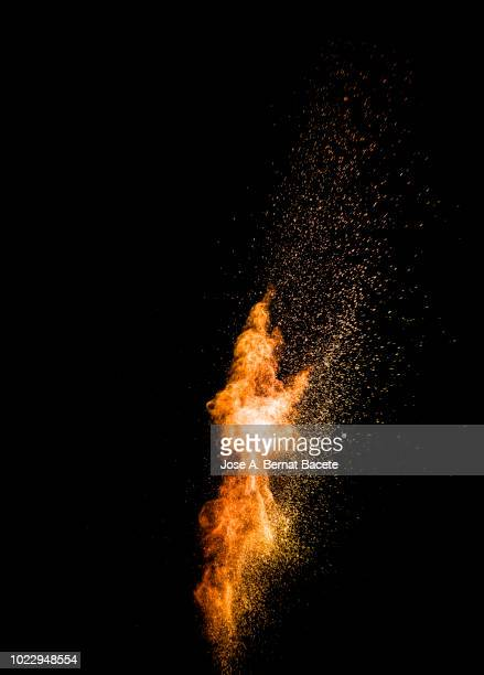 explosion by an impact of a cloud of particles of powder of color red and yellow on a black background. - fogo - fotografias e filmes do acervo