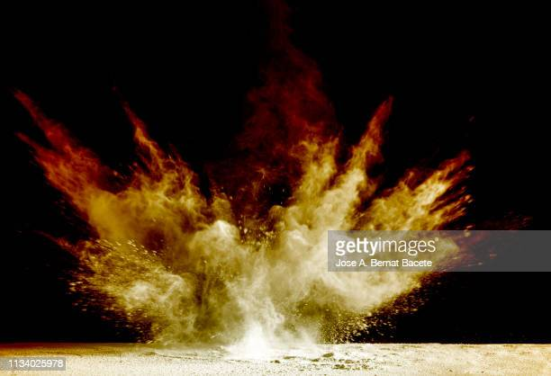 explosion by an impact of a cloud of particles of powder of color red and yellow on a black background. - 爆発物 ストックフォトと画像