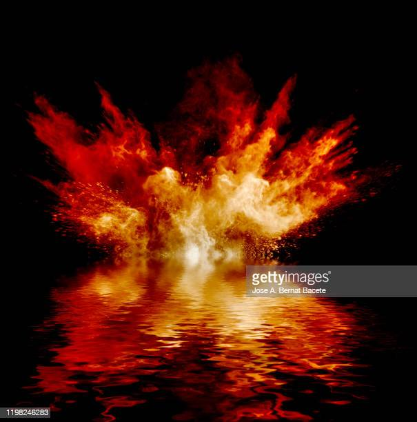 explosion by an impact of a cloud of particles of powder of orange color on a black background reflected on the water. - 爆発物 ストックフォトと画像