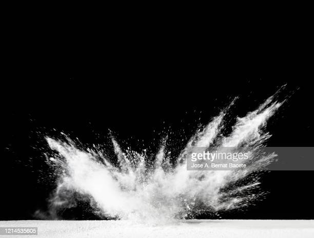 explosion by an impact of a cloud of particles of powder of white color on a black background. - talcum powder stock pictures, royalty-free photos & images