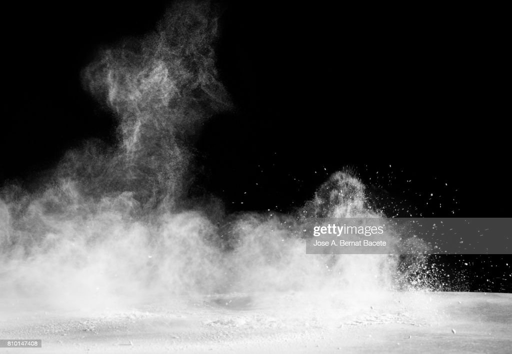 Explosion of a cloud of powder of particles of color white and a black background : Stock Photo