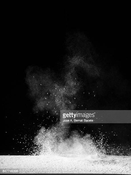Explosion of a cloud of powder of particles of color white and a black background