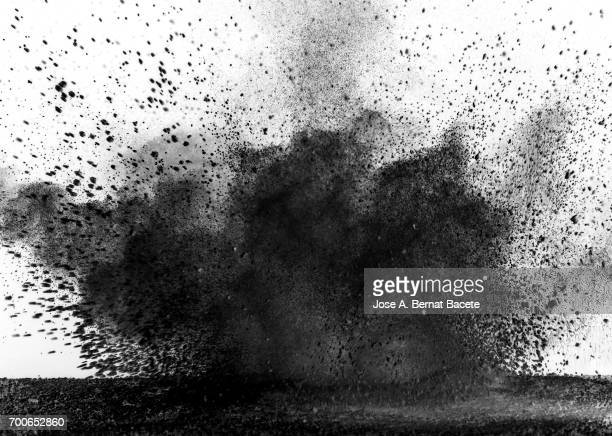 Explosion of a cloud of powder of particles of colors gray and black and a white background
