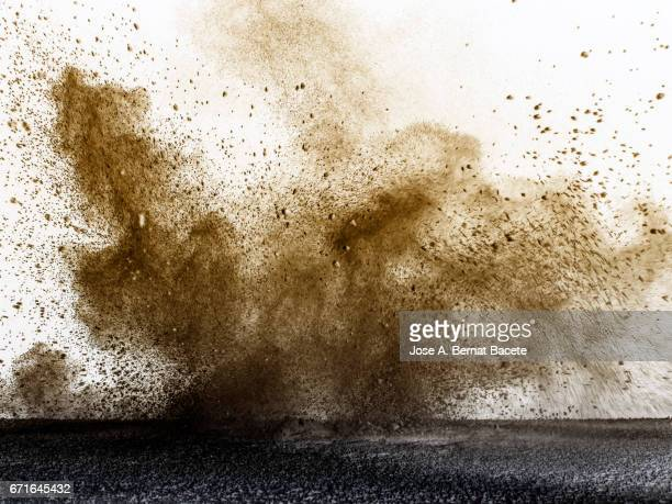 explosion of a cloud of powder of particles of colors gray and brown and a white background - detonate stock photos and pictures