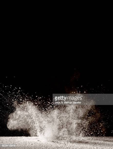 Explosion of a cloud of powder of particles of colors gray and white and a black vintage background