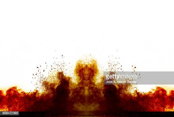 Explosion of a cloud of powder of particles of  colors red and orange on a white background