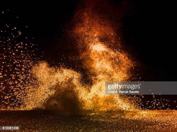 Explosion of a cloud of powder of particles of colors red and yellow and a black background