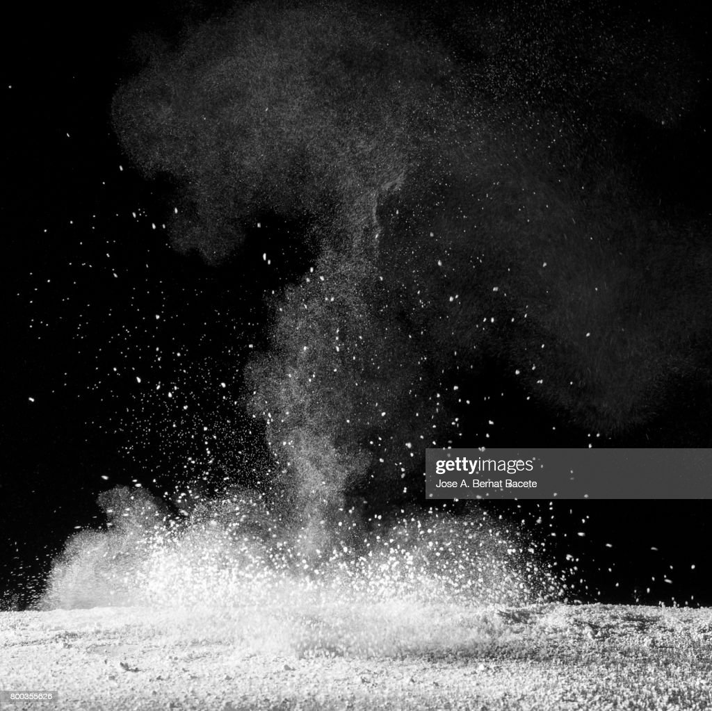 Explosion of a cloud of powder of particles of colors white  and a black background : Stock Photo