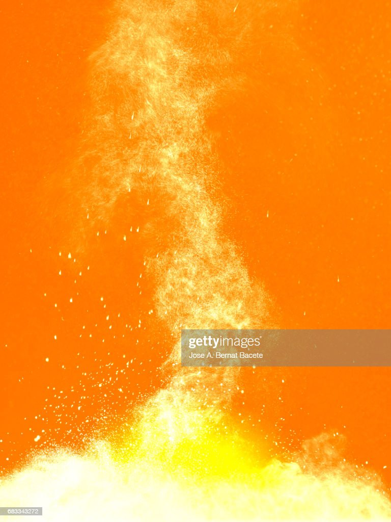 Explosion of a cloud of powder of particles of colors white and yellow and a orange background : Stock Photo