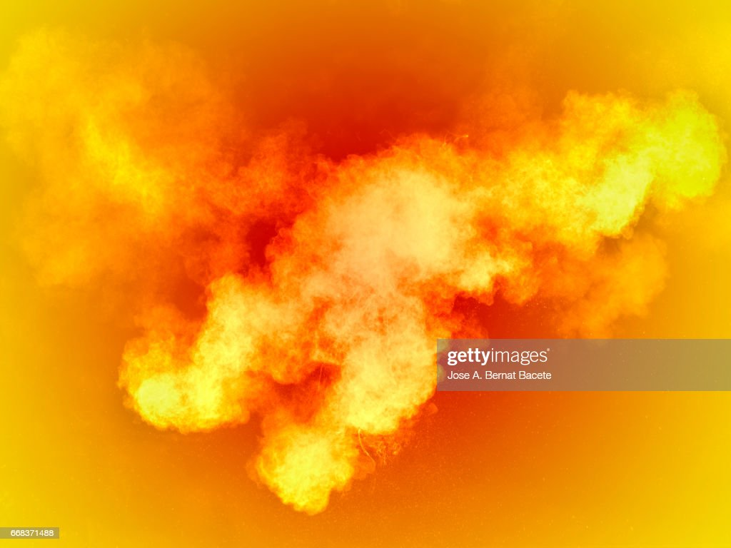 Explosion of a cloud of powder of particles of  colors yellow and orange on a orange background : Stock Photo