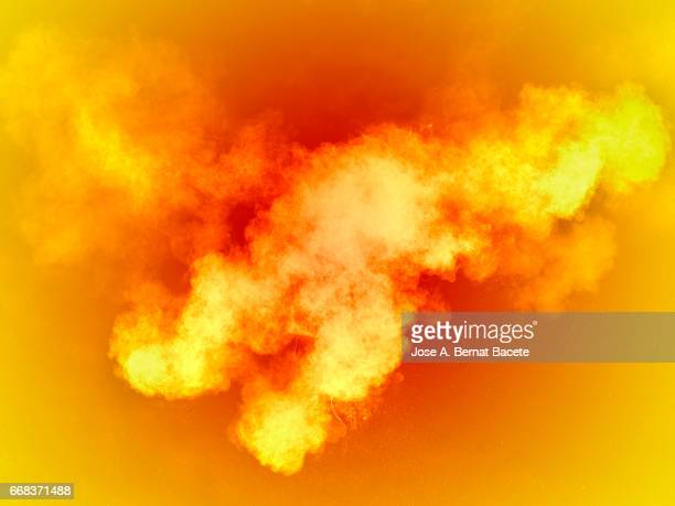 Explosion of a cloud of powder of particles of  colors yellow and orange on a orange background