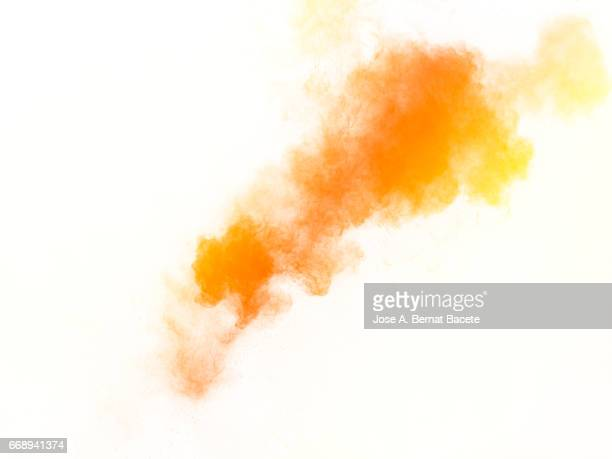 Explosion of a cloud of powder of particles of  colors yellow and orange on a white background