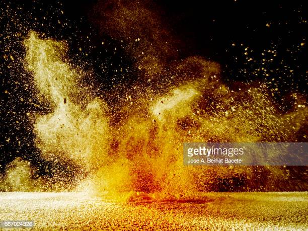 Explosion of a cloud of powder of particles of orange and yellow color on a black background