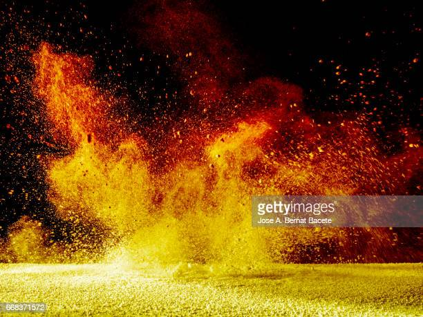 explosion of a cloud of powder of particles of orange and yellow color on a black background - explosives stock photos and pictures